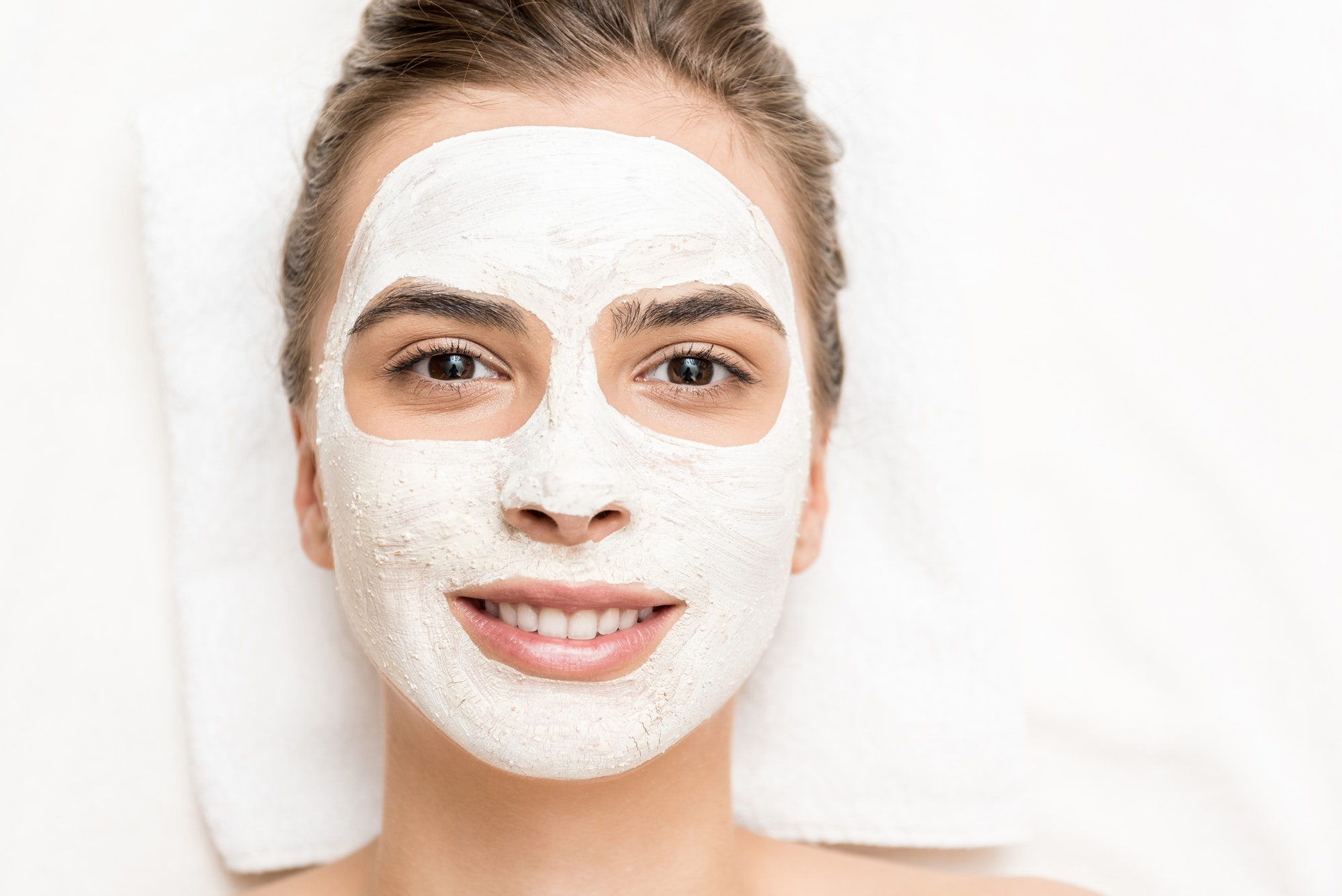 spa therapy for smiling woman receiving facial mask